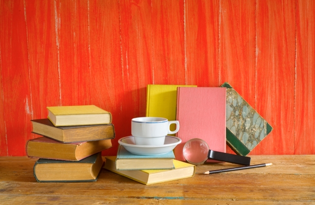 vintage books with cup of coffee,magnifying glass, free copy space