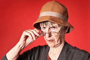 Old woman looks disapprovingly over spectacles at camera